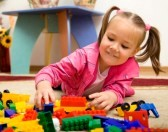 11872448-little-girl-is-playing-with-building-bricks-in-preschool-while-laying-on-floor